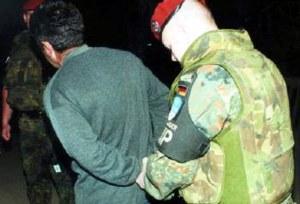 Wegen des Überschreitens der nächtlichen Ausgangssperre haben Feldjäger in der Innenstadt von Prizren einen Mann auf die MP-Station gebracht. Zur Durchsuchung und Datenerfassung nehmen sie ihm die Handschellen ab.